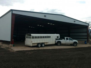 large metal barn with a truck and horse trailer